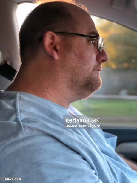 side view of man driving car - rowena miller stock photos and pictures
