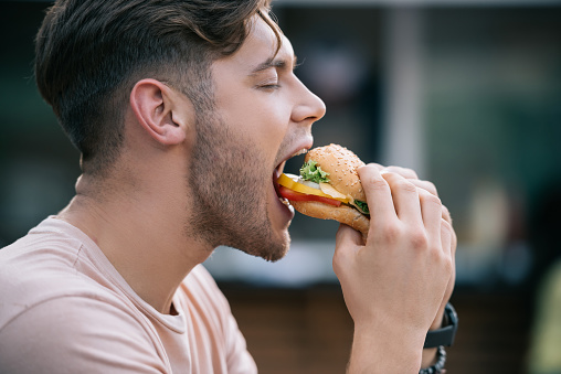 side view of man eating tasty burger with closed eyes 1017325802