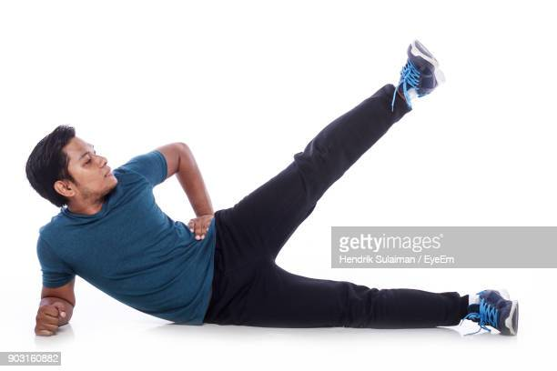 side view of man exercising against white background - lying on side stock pictures, royalty-free photos & images