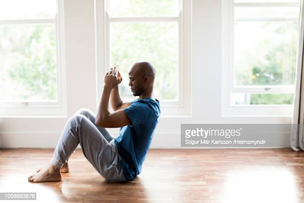 side view of man exercising on hardwood floor - home workout stock pictures, royalty-free photos & images