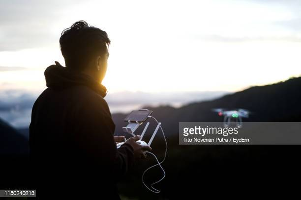 side view of man flying drone over mountain against sky during sunset - remote control helicopter stock photos and pictures