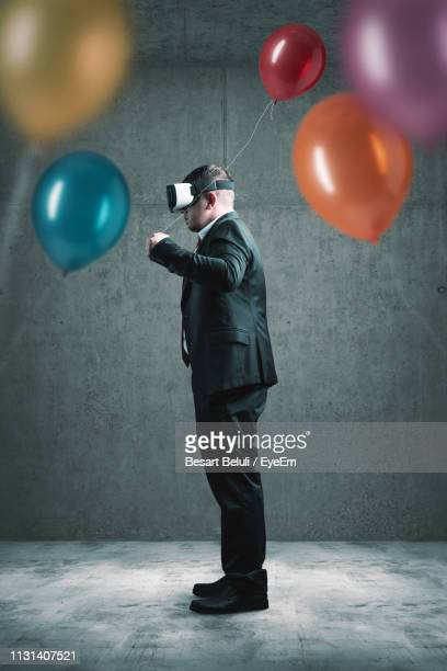 86d35ffa5d2f Side View Of Man Holding Balloon While Using Virtual Reality Simulator  Against Wall