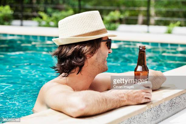 Side view of man holding beer bottle in swimming pool