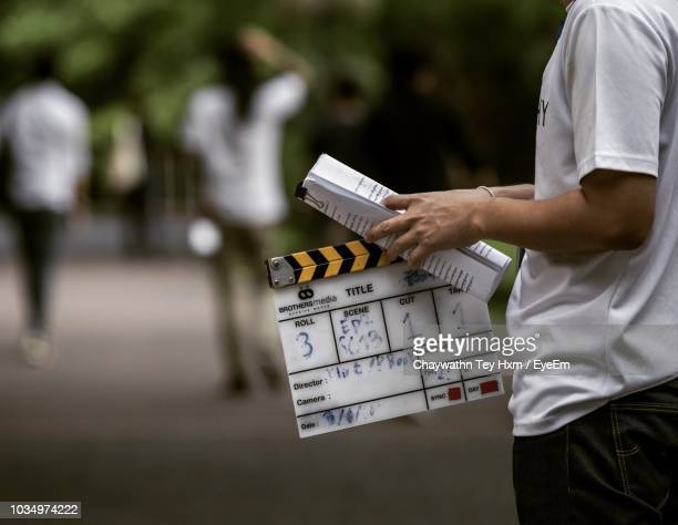 side view of man holding film slate while standing on footpath - clapboard stock pictures, royalty-free photos & images