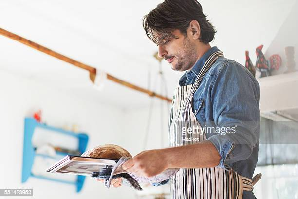 Side view of man holding freshly baked bread in tray at home