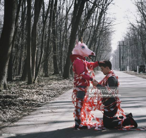 Side View Of Man Holding Friend Wearing Unicorn Mask On Road