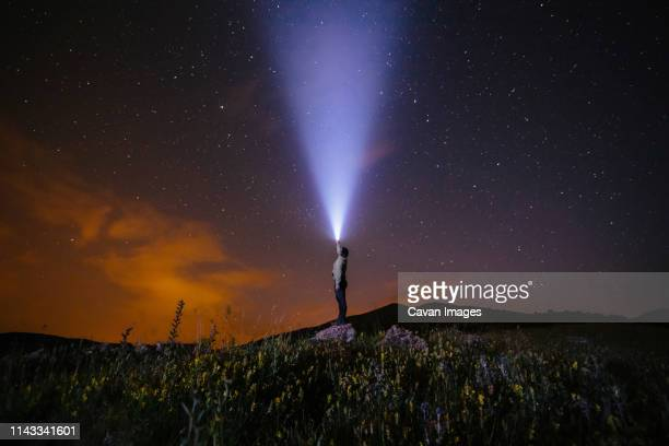 side view of man holding illuminated flashlight while standing on hill against star field at night - flashlight stock pictures, royalty-free photos & images