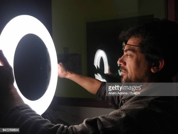 Side View Of Man Holding Illuminated Ring