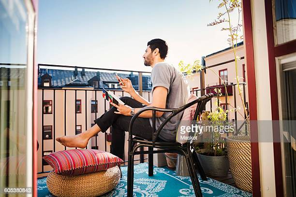 Side view of man holding smart phone and guidebook while looking away at balcony