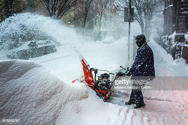 Side View Of Man Holding Snowblower During Snowfall