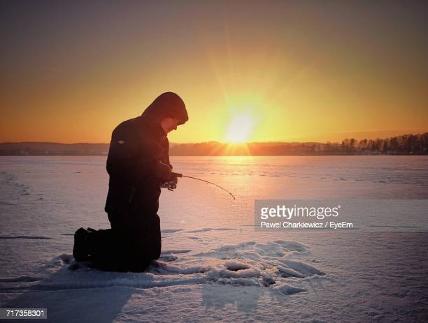 Side View Of Man Ice Fishing During Sunset