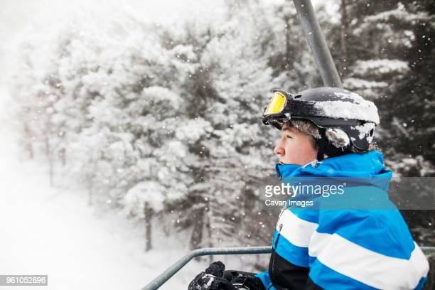 side view of man in ski lift against snow covered trees - ski lift stock pictures, royalty-free photos & images