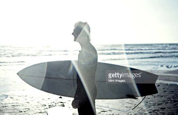 Side view of man in wetsuit standing by the ocean, carrying surfboard.
