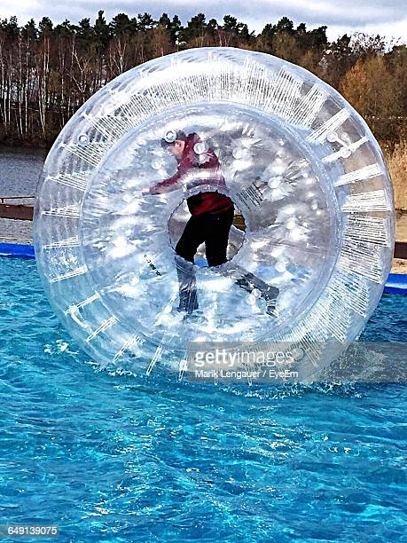 Side View Of Man In Zorb Ball Floating In Lake