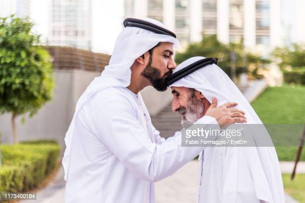 side view of man kissing grandfather wearing dish dash on footpath at park - traditional clothing stock pictures, royalty-free photos & images