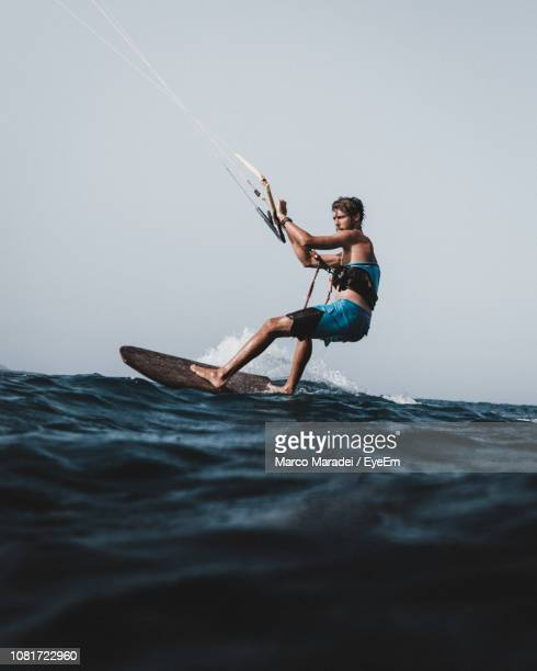 side view of man kiteboarding in sea against clear sky - sport aquatique photos et images de collection