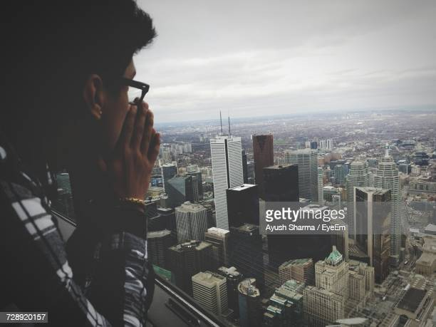 Side View Of Man Leaning On Window Sill While Looking At City Against Cloudy Sky