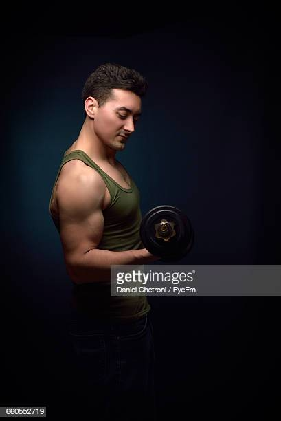 Side View Of Man Lifting Weights Against Black Background