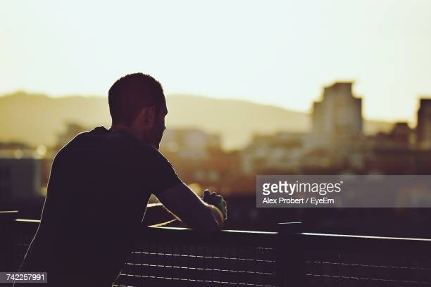 Side View Of Man Looking At Cityscape While Standing In Balcony During Sunset