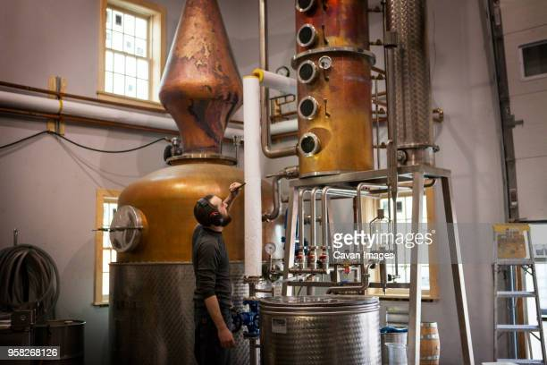 Side view of man looking at machinery at distillery