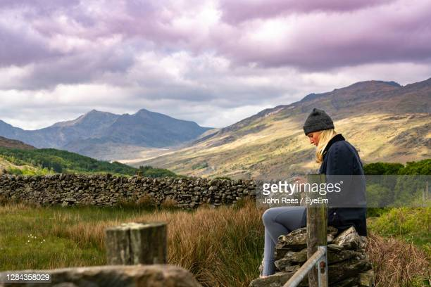side view of man looking at mountains against cloudy sky - vacations stock pictures, royalty-free photos & images