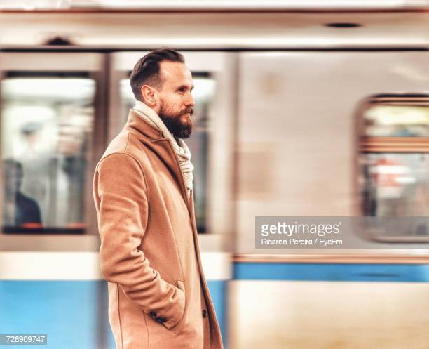 Side View Of Man Looking Away While Standing Against Train At Subway Station