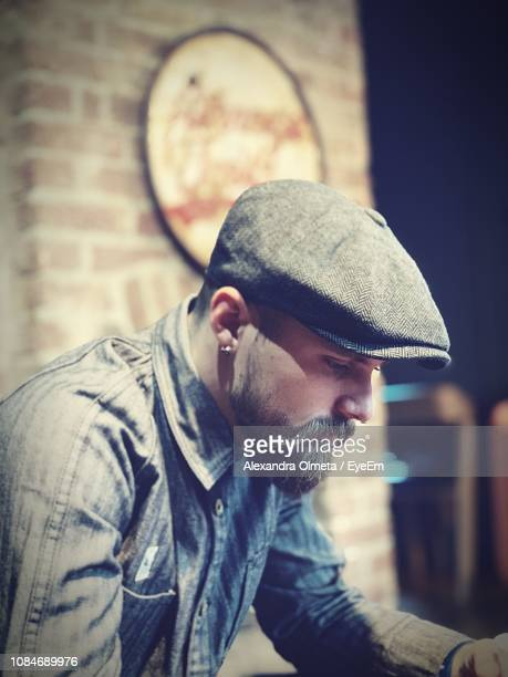 side view of man looking down - flat cap stock photos and pictures