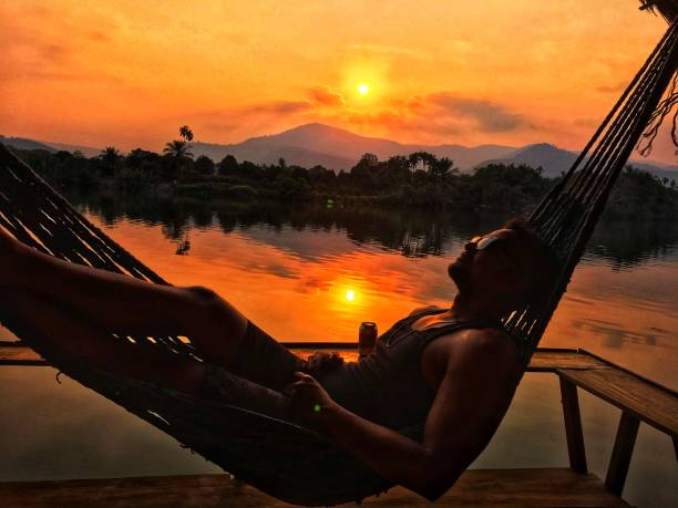 Side View Of Man Lying On Hammock Against Lake During Sunset