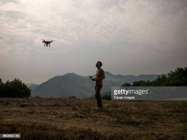 side view of man operating drone through remote control against mountains - hovering stock pictures, royalty-free photos & images