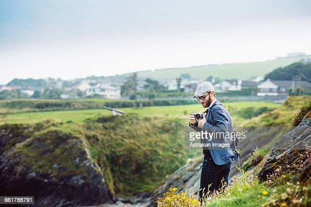 side view of man photographing on hill - republic of ireland stock pictures, royalty-free photos & images