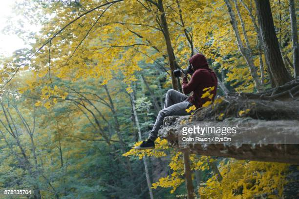 Side View Of Man Photographing Through Camera While Sitting On Cliff