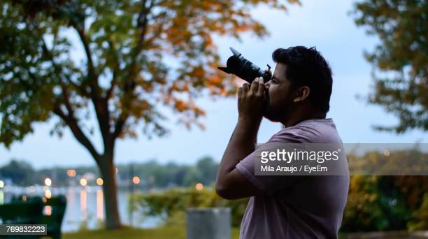 Side View Of Man Photographing Using Camera