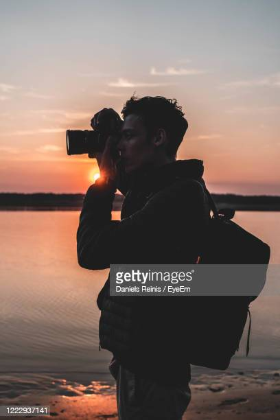 side view of man photographing while standing at beach during sunset - photographer stock pictures, royalty-free photos & images