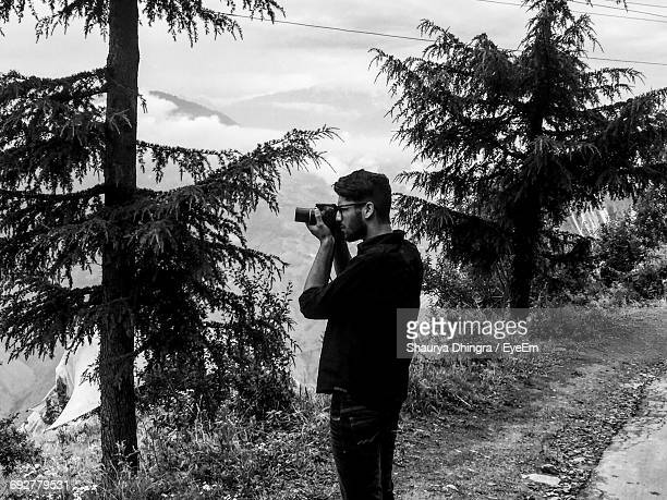 Side View Of Man Photographing While Standing By Tree In Forest