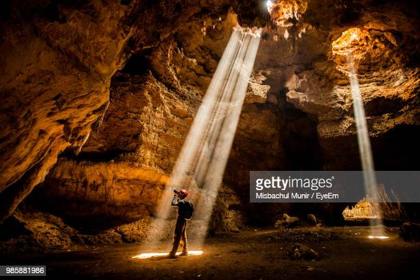 side view of man photographing while standing in caves - geology stock pictures, royalty-free photos & images
