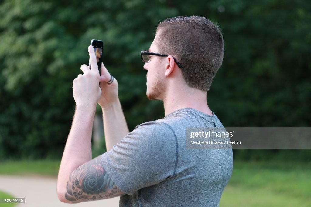 Side View Of Man Photographing While Standing On Field : Photo