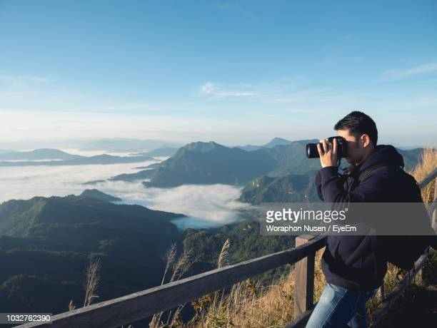 Side View Of Man Photographing While Standing On Mountain Against Sky