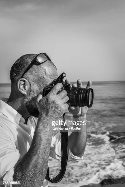 Side View Of Man Photographing With Camera By Sea