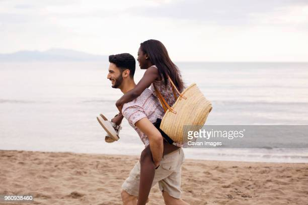 Side view of man piggybacking woman on beach