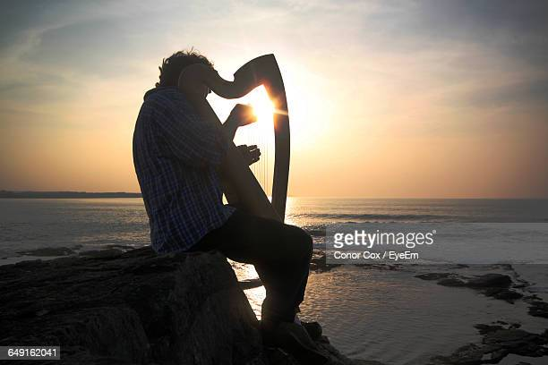 Side View Of Man Playing Harp While Sitting On Rock By Sea During Sunset