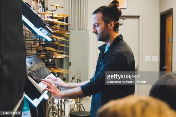 side view of man playing keyboard instrument - only mid adult men stock pictures, royalty-free photos & images