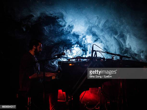 Side View Of Man Playing Piano During Music Concert