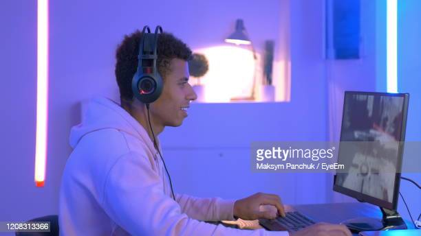 side view of man playing video game in illuminated room - gamer stock pictures, royalty-free photos & images