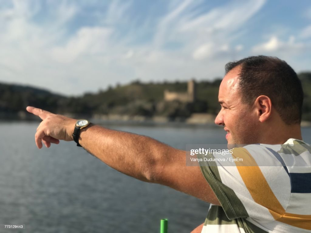 Side View Of Man Pointing Against Sky : Photo