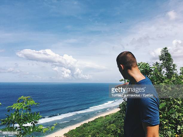 Side View Of Man Pointing Finger Towards Sea