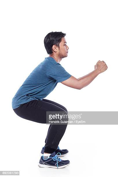 Side View Of Man Practicing Squats Against White Background