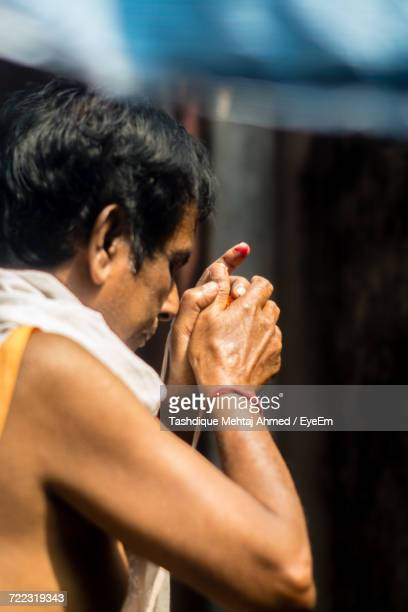 side view of man praying at temple - guwahati stock photos and pictures
