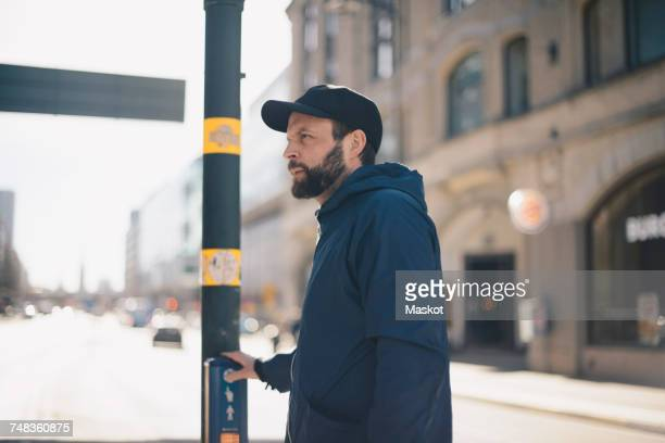 Side view of man pushing button on pedestrian crossing sign in city during sunny day