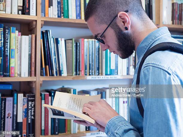 Side View Of Man Reading Book In Library