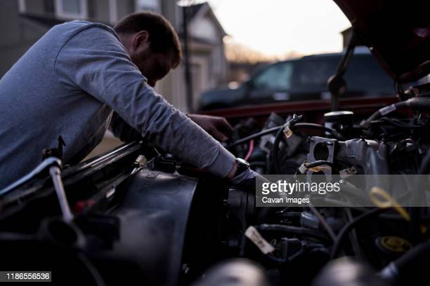 side view of man repairing car's engine during sunset - adjusting stock pictures, royalty-free photos & images